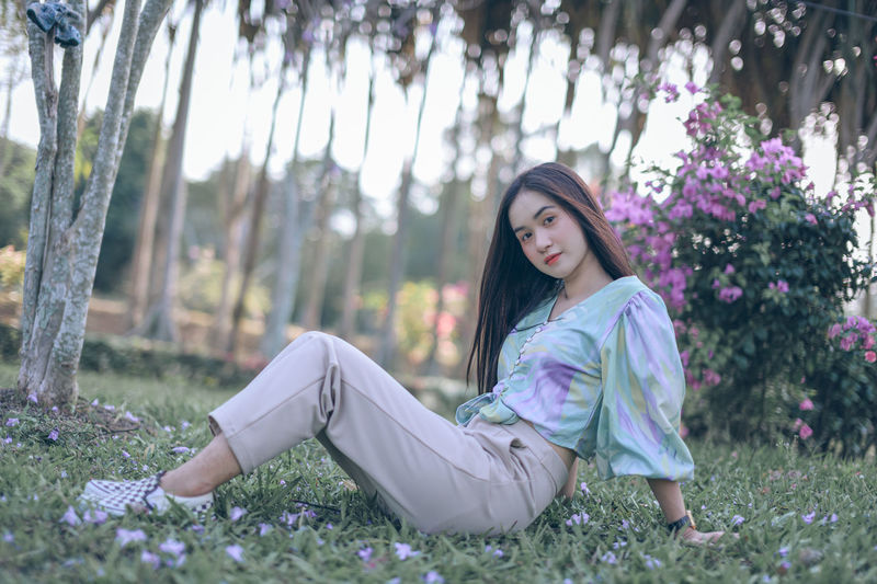 Portrait of beautiful woman sitting on land in park