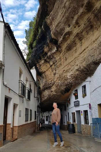 Full Length Of Woman Standing Amidst Residential Buildings Below Mountain