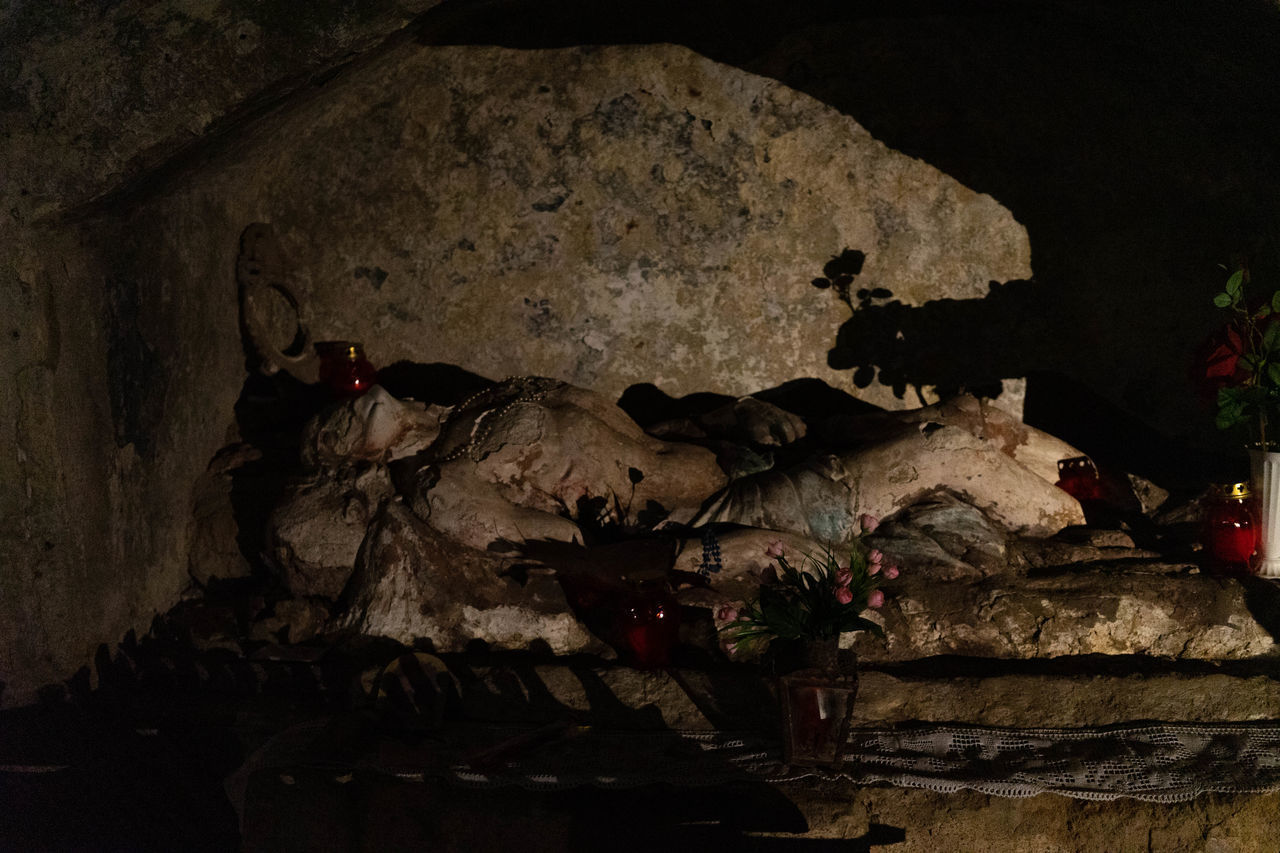 no people, indoors, cave, human representation, representation, nature, close-up, art and craft, architecture, creativity, night, history, the past, solid, wall, still life, male likeness, craft, plant
