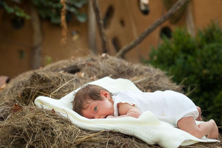 Cute Baby Girl Lying On Hay Bale