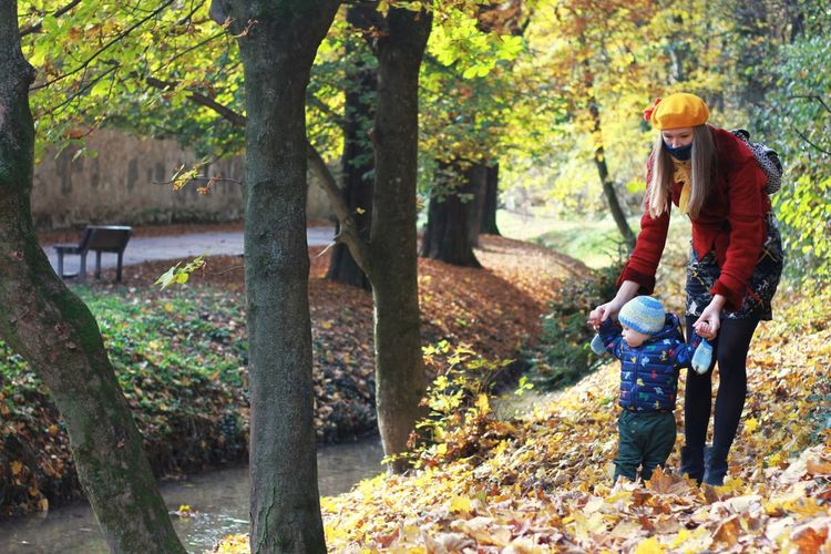 Man and son in forest during autumn