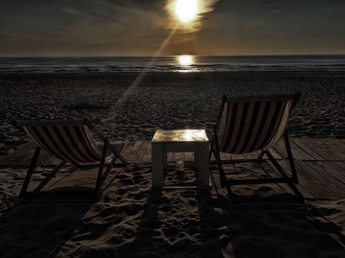 Chairs and table on beach against sky during sunset