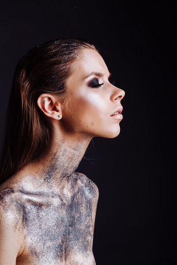 Shirtless Young Woman With Silver Glitter On Her Body Against Black Background