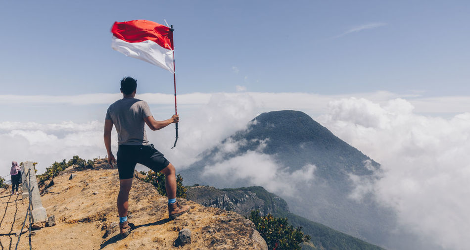 Rear view of man holding flag while standing on mountain against sky