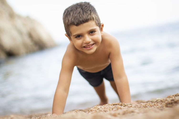 Beach Boys Child Childhood Day Happiness Innocence Land Leisure Activity Looking At Camera Males  Men One Person Outdoors Portrait Pre-adolescent Child Sand Sea Shirtless Smiling Water