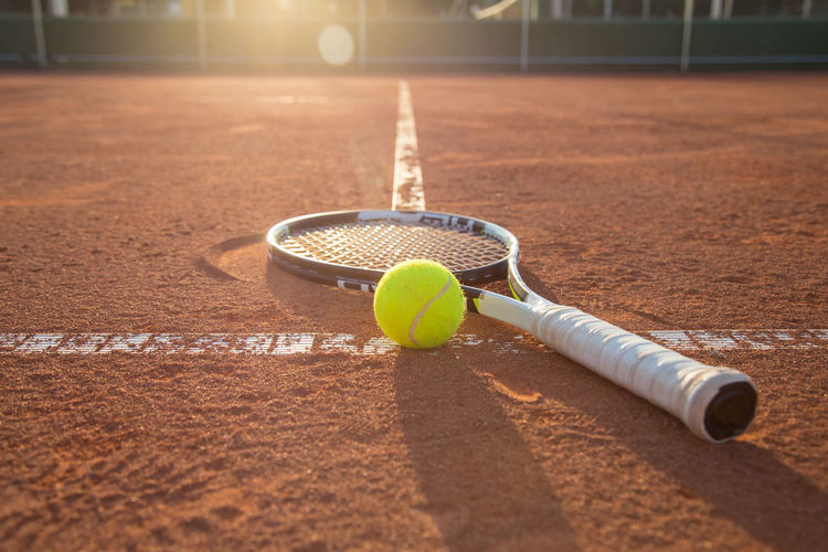 Close-Up Of Tennis Racket And Ball On Court During Sunset