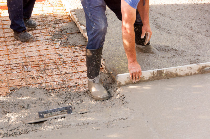 Low section of manual worker scrapping on cement at construction site