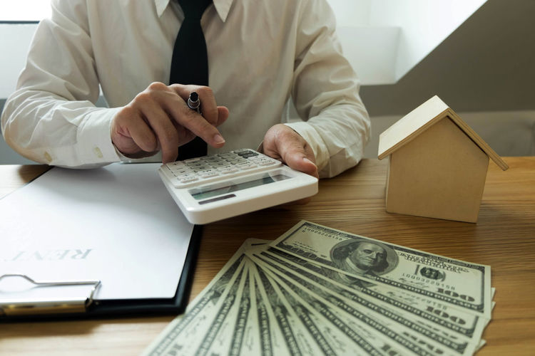 Midsection of businessman using calculator graph on table
