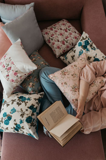 High angle view of woman reading book sitting on sofa at home
