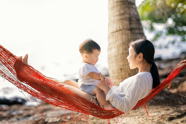 Mother with cute son sitting on hammock at beach