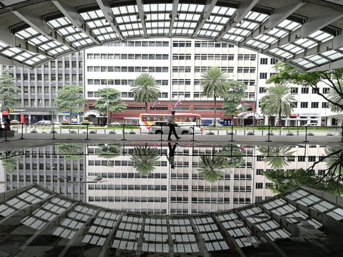 Reflection Of Man And Building On Puddle In City