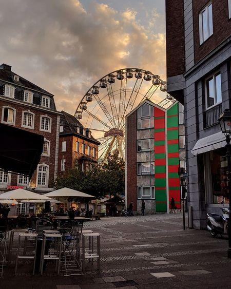 Ferris wheel by buildings in city against sky