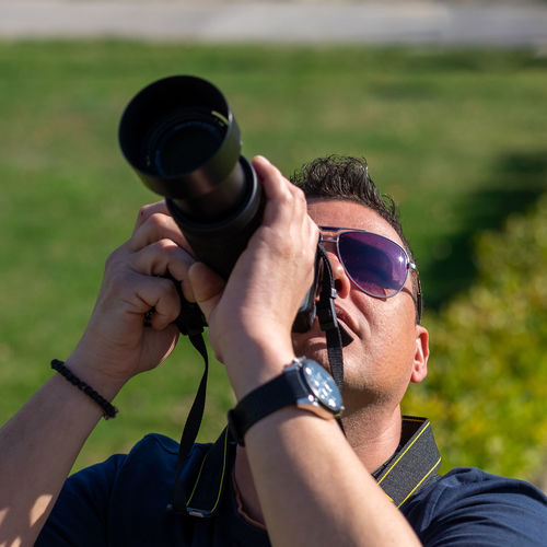 Close-up of man photographing with camera at park