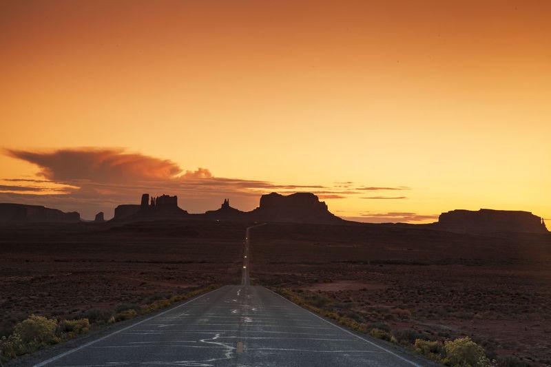 Empty Road Leading Towards Rock Formations Against Orange Sky