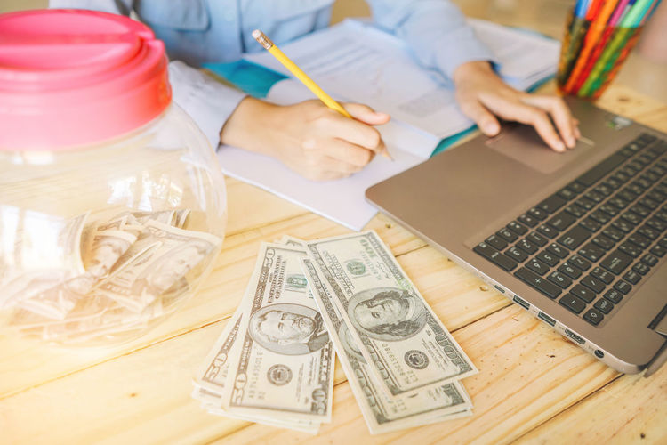 High angle view of businessman working with money and laptop on table