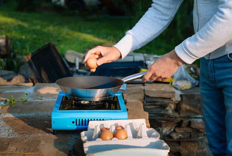 Midsection of man preparing food on camping stove