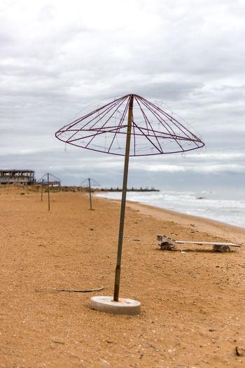 Umbrella on beach against sky