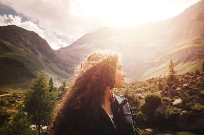 Young woman with curly hair enjoying the tranquility of the sunset in the dolomite mountains in Northern Italy Dolomites, Italy Tranquility Adult Beauty In Nature Environment Hair Hairstyle Headshot Leisure Activity Lifestyles Long Hair Mountain Mountain Range Nature One Person Optimism Outdoors Portrait Real People Scenics - Nature Sky Travel Destinations Women Young Adult Young Women Summer Road Tripping