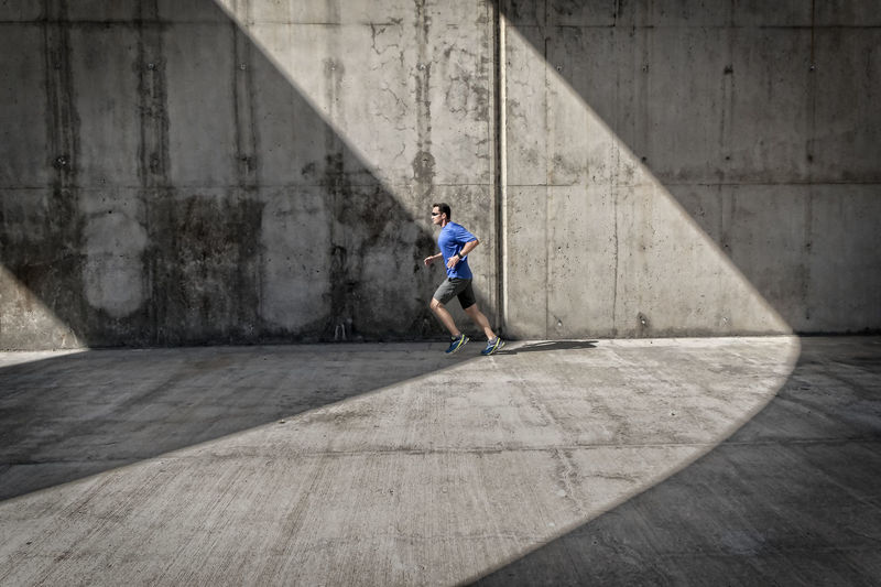Side view of male runner with blue shirt and smart watch, who runs under concrete arcades. Activity Athleticism Built Structure Concrete Day Exercising Healthy Lifestyle Jogger Jogging Jogging Time Leisure Activity Lifestyles Men Motion One Person Outdoors Runner Shadow Skill  Sport Sports Training Sunlight Vitality Wall The Week On EyeEm