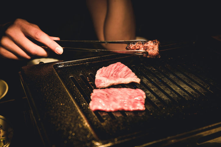 Cropped hand roasting food on barbecue grill