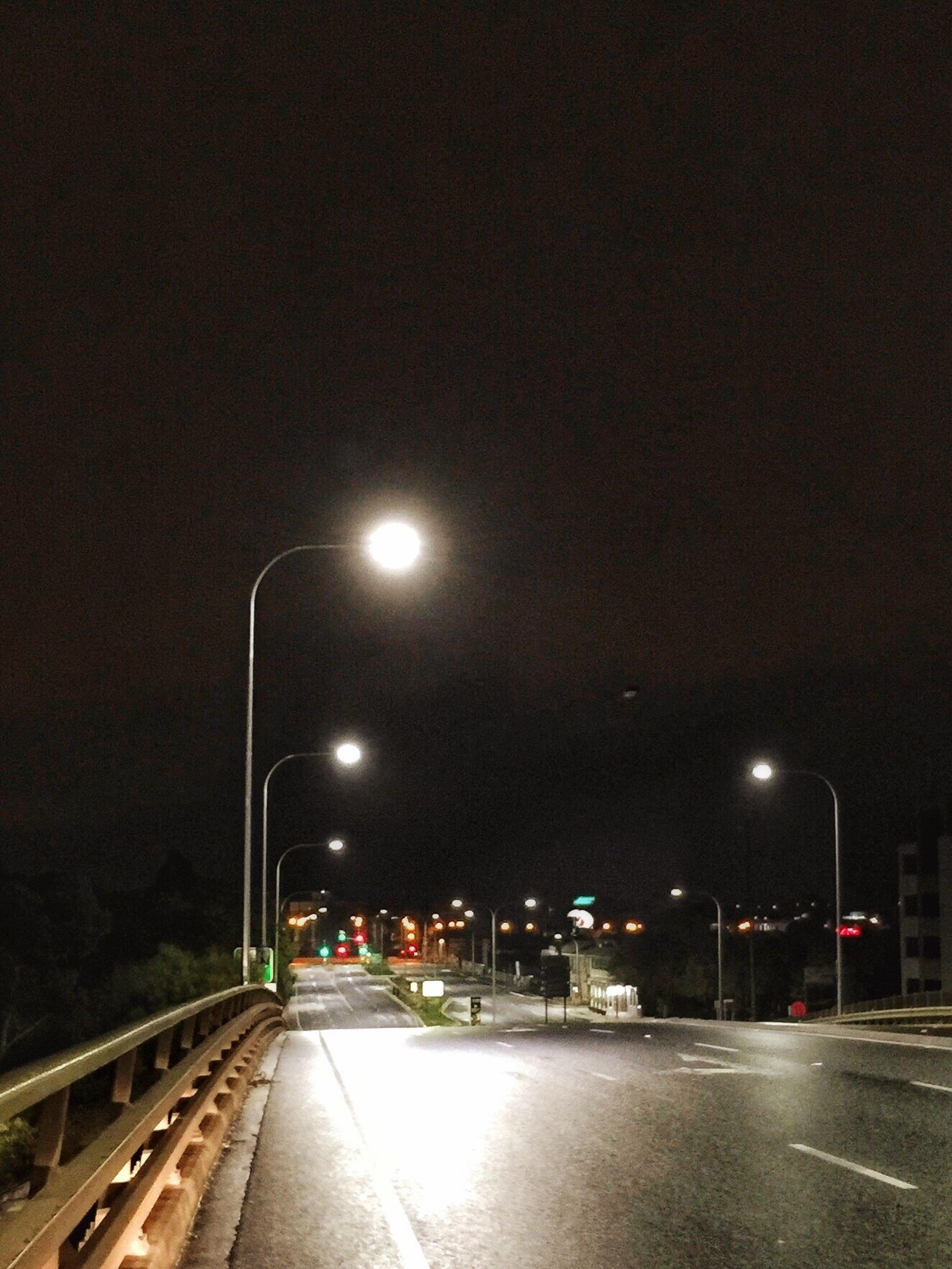 night, illuminated, street light, road, the way forward, transportation, street, lighting equipment, road marking, sky, diminishing perspective, architecture, built structure, building exterior, vanishing point, city, clear sky, car, outdoors, empty road