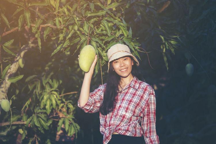 Portrait of female farmer holding mangoes in farm