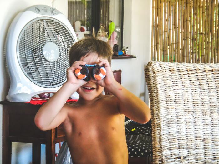 Shirtless boy looking through toy binoculars