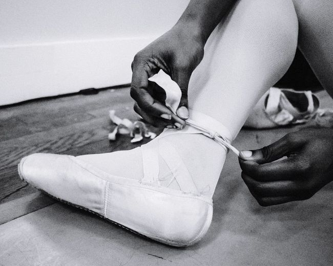 Low section of ballet dancer wearing shoe at studio