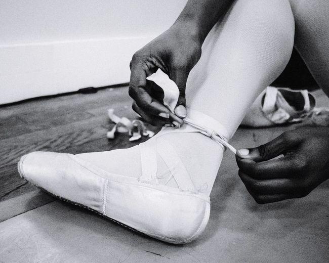 Low Section Of Ballet Dancer Wearing Shoe At Studio