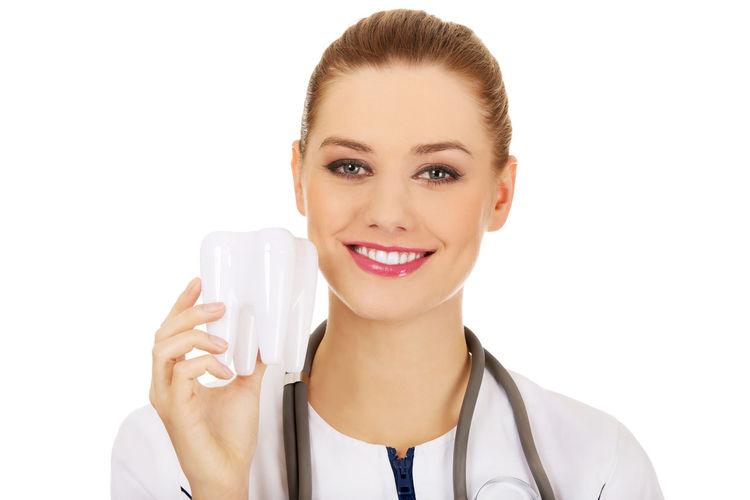 Portrait of female doctor holding dentures against white background