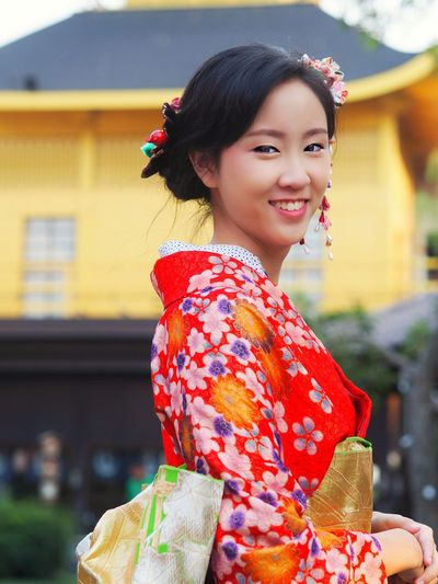 Portrait Of Smiling Young Woman In Traditional Clothing Standing Against House