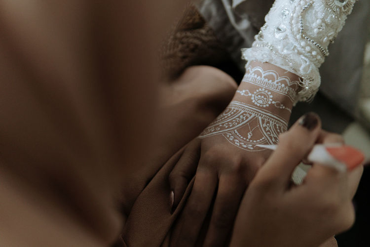 Cropped image of woman applying henna tattoo on bride hands