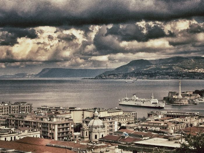 View of town by sea against cloudy sky