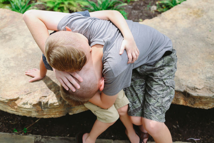 Brothers embracing while sitting on rock