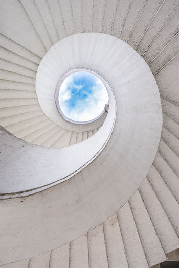 Spiral staircase and cloudy sky