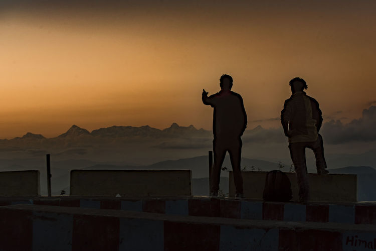 Rear view of silhouette men standing on mountain against orange sky