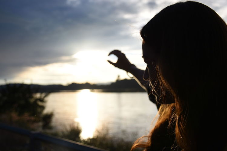 Woman gesturing by lake during sunset