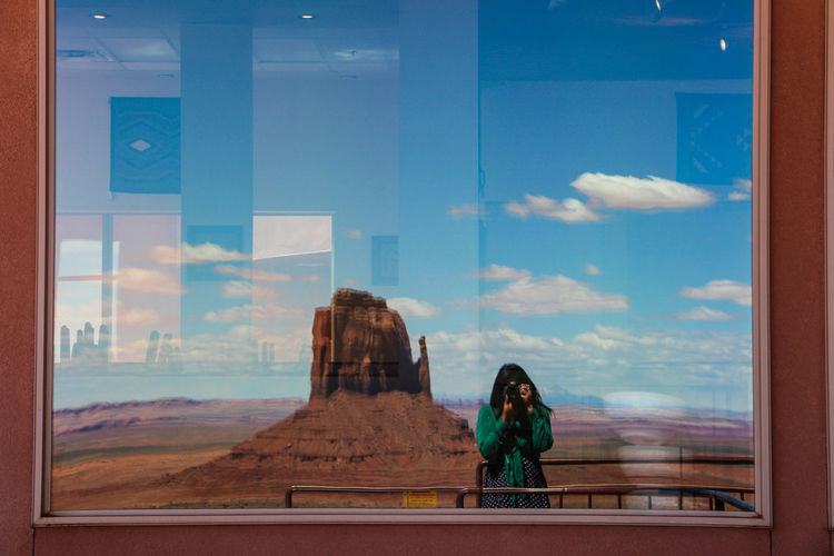 Window One Person Glass - Material Transparent Lifestyles Sky Women Day Reflection Standing Indoors  Real People Cloud - Sky Leisure Activity Adult Looking Long Hair Hair Nature Hairstyle Contemplation Monument Valley