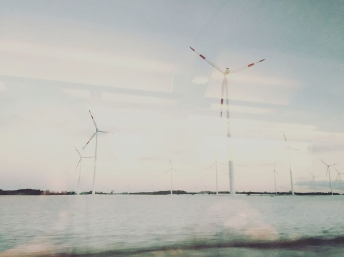 Windmills on field against sky