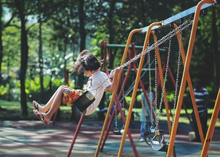 Side view of girl playing on swing at playground