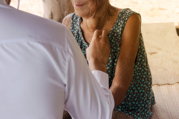 Midsection Of Doctor Checking Female Patient On Seat