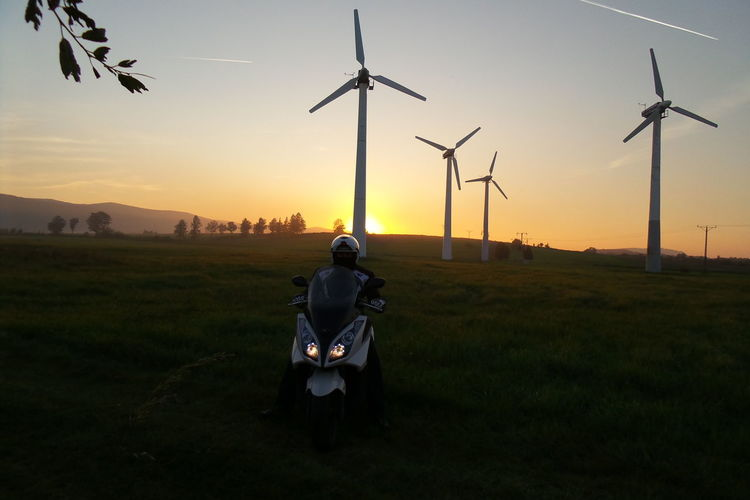 Kymco Alternative Energy Beauty In Nature Day Field Fuel And Power Generation Full Length Grass Industrial Windmill Men Nature One Person Outdoors People Real People Rear View Renewable Energy Sky Standing Sunset Technology Wind Power Wind Turbine Windmill