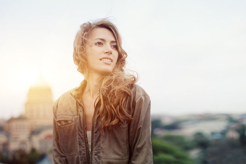 A happy curly-haired girl in a brown leather jacket walks against the backdrop of the city. Smile Happiness Autumn Caucasian Girls EyeEmNewHere Happy Beautiful Woman Beauty Close-up Emotion Hair Hairstyle Happiness Leather Jacket Lifestyles Long Hair Looking One Person Outdoors Portrait Smiling Standing Summer Sunshine Women Young Adult Young Women