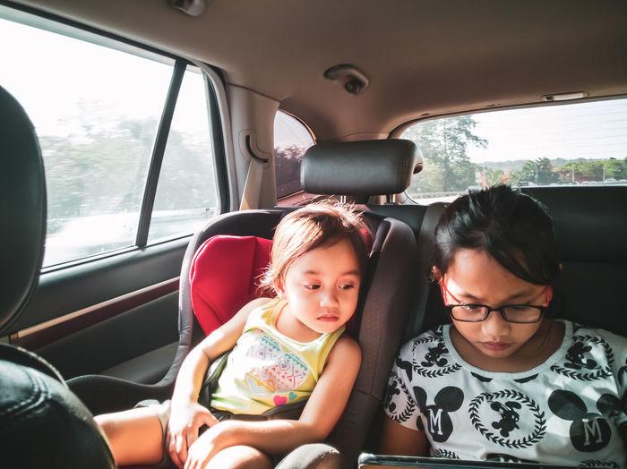 Siblings looking at digital tablet while sitting in car
