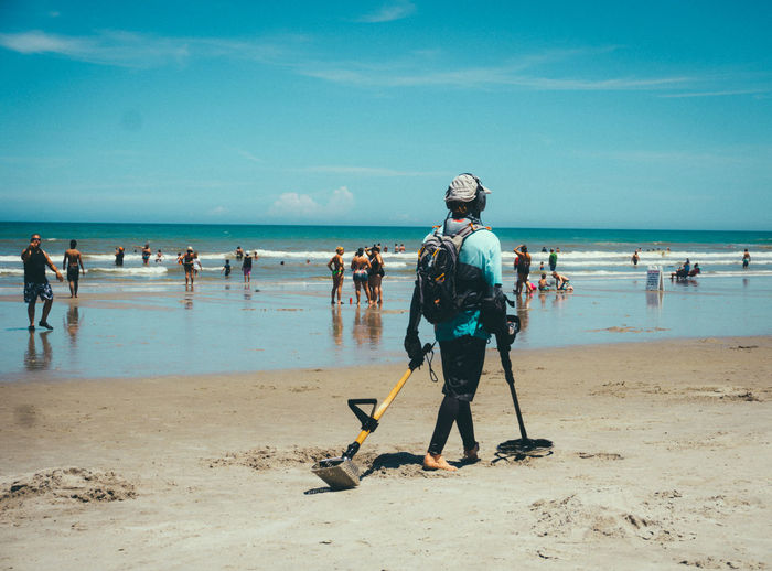Person With Equipment Walking At Beach Against Blue Sky