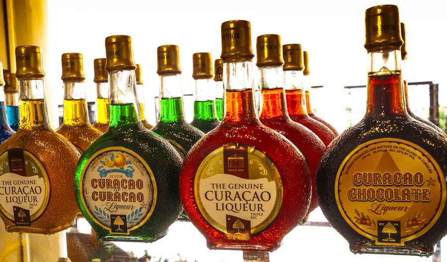 Curaçao is a liqueur flavored with the dried peel of the laraha citrus fruit, grown on the island of Curaçao. Arrangement Capital Letter Collection Communication Creativity Curacao Group Of Objects In A Row Information Information Sign Laraha Citrus Fruit Large Group Of Objects Liqueur Liqueur Bottle Man Made Object Non-western Script Repetition Retail  Retail Display Text Western Script Willemstad