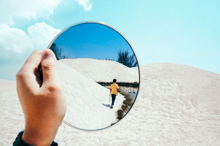 Cropped hand holding mirror with reflection of boy walking on sand at desert