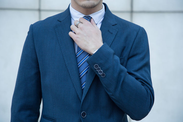 Midsection Of Businessman Standing Against Wall