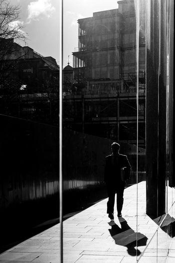 Reflection of man walking on street