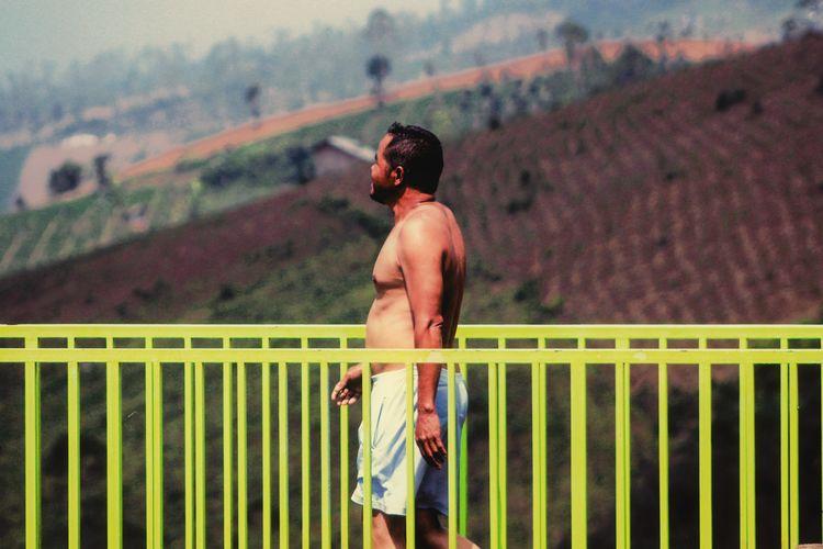 Rear view of shirtless man looking at railing